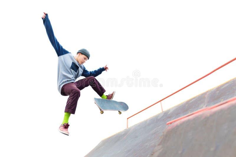 盖帽的少年溜冰板者做与一个跃迁的一个把戏在skatepark的舷梯 被隔绝的溜冰者和舷梯  免版税库存照片