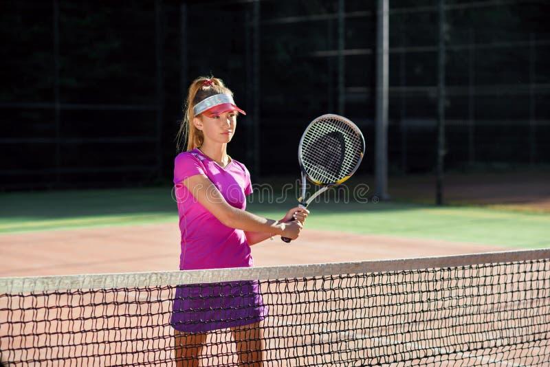 盖帽的年轻女人和在训练期间的网球一致的服务的网球在室外网球场 相当运动 免版税库存图片