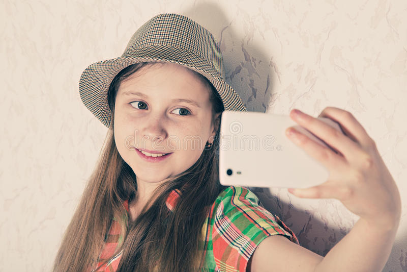 盖帽的快乐的女孩和在智能手机的制造selfie 图库摄影