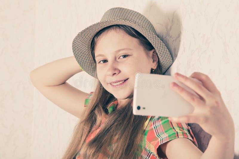 盖帽的快乐的女孩和在智能手机的制造selfie 免版税图库摄影