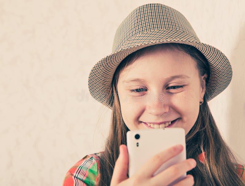 盖帽的快乐的女孩和在智能手机的制造selfie 免版税库存照片