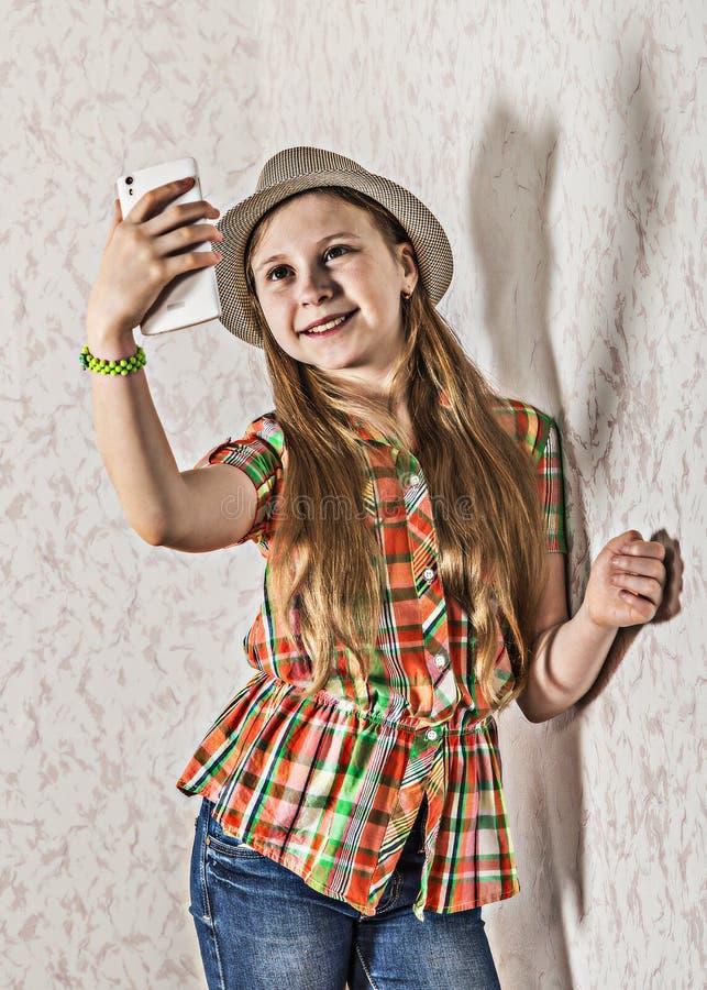 盖帽的快乐的女孩和在智能手机的制造selfie 库存图片