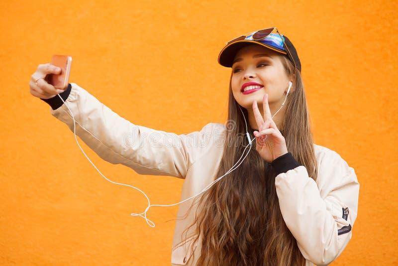 盖帽的秀丽年轻行家女孩和黄色太阳镜由智能手机做selfie 免版税库存照片