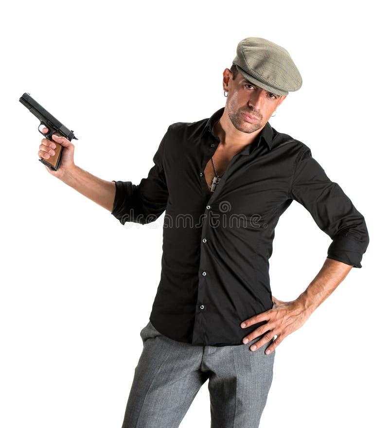 盖帽的英俊的人有枪的 免版税库存图片
