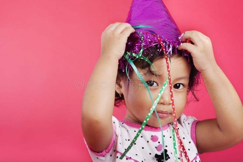 盖帽逗人喜爱女孩当事人佩带 免版税库存图片