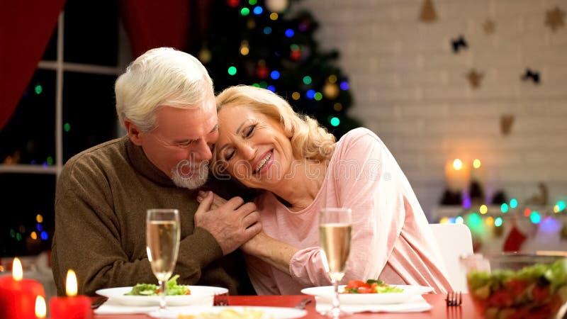 盖年轻妻子的丈夫用舒适格子花呢披肩,庆祝Xmas前夕,关系 库存照片