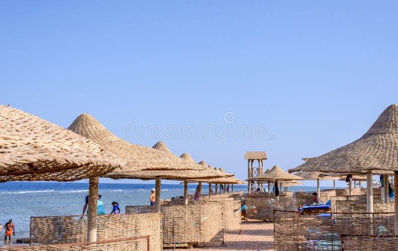 盖的沙滩伞和可躺式椅椅子 免版税图库摄影