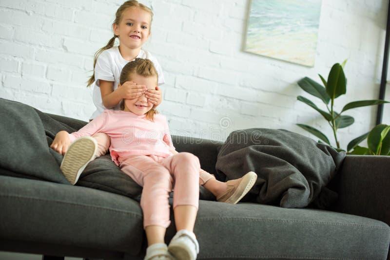 盖眼睛的可爱的小孩对沙发的姐妹 免版税库存照片