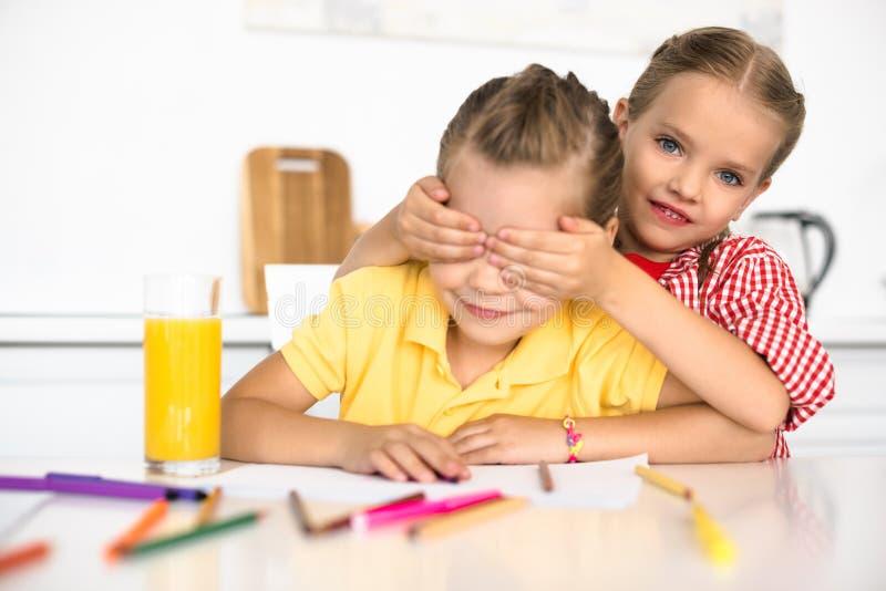 盖眼睛的逗人喜爱的小孩对姐妹在桌上用铅笔和纸画的 库存图片