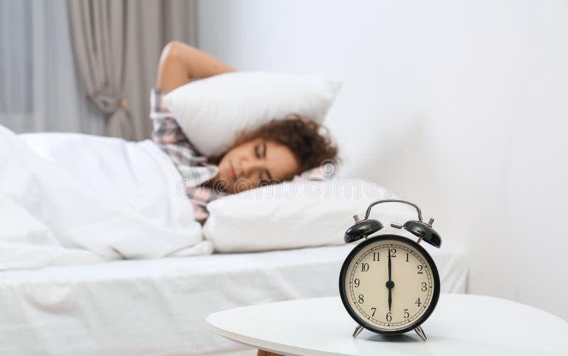 盖耳朵的年轻非裔美国人的妇女用枕头,当掩藏从闹钟时 哔哔 免版税库存照片