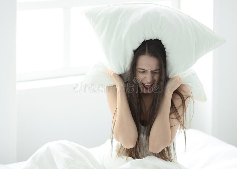 盖耳朵的懊恼年轻女人用枕头,阻拦声音,遭受噪声,在床上,睡眠的问题 库存照片