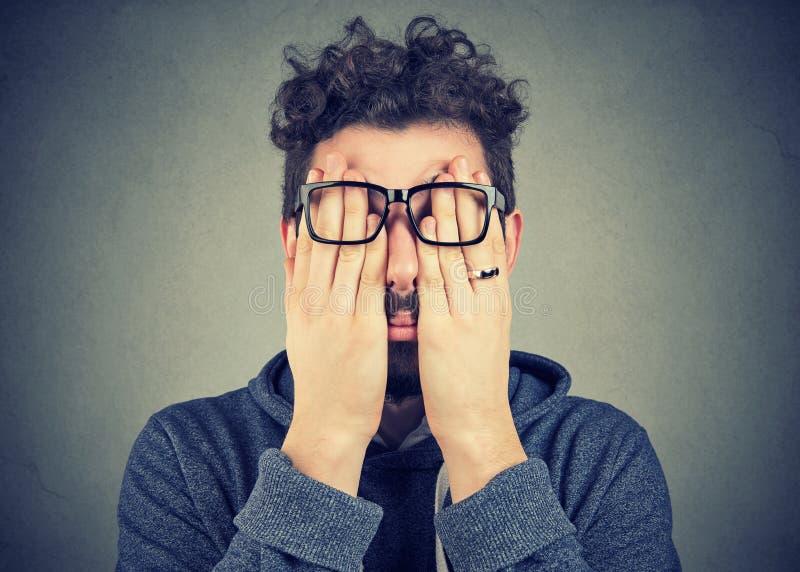 盖面孔的玻璃的年轻人注视用两只手 免版税库存图片