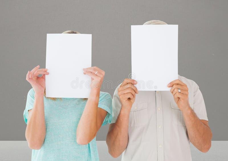 盖他们的在纸后的男人和妇女面孔反对灰色背景 库存图片