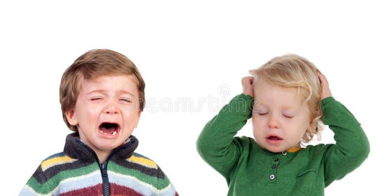 盖他的耳朵的小孩哭泣和别的 免版税库存图片