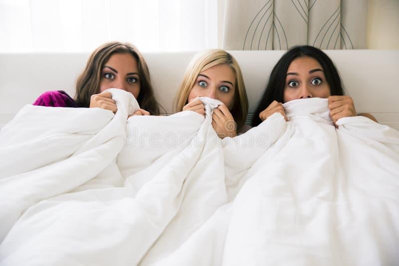 盖他们的面孔的害怕的女朋友用毯子 免版税库存图片
