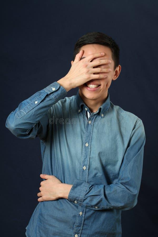 盖他的面孔的惊奇的年轻亚裔人由棕榈 库存照片
