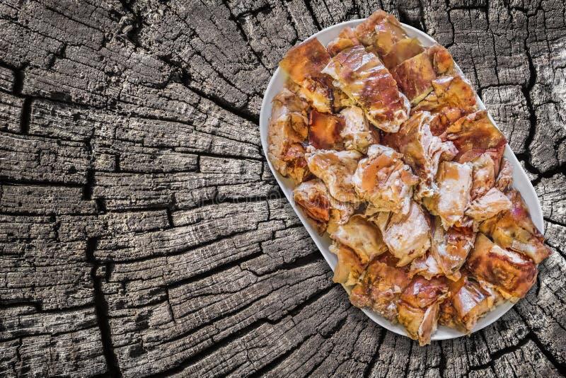 满盘唾液在切片的烤猪肉裁减在作为被即兴创作的野餐桌的老破裂的树桩 免版税库存照片