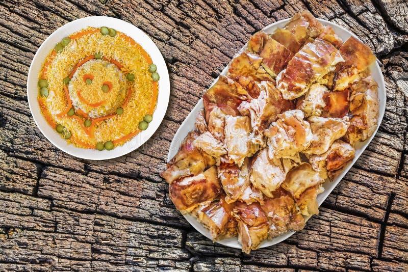 满盘唾液烤了与碗的猪肉切片在老破裂的树桩的奥利维尔沙拉,被即兴创作的野餐桌 库存图片