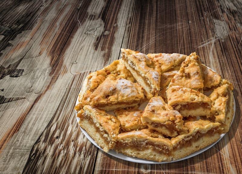 满盘在老破裂的被剥皮的木庭院表上的懒惰苹果饼切片 免版税库存图片