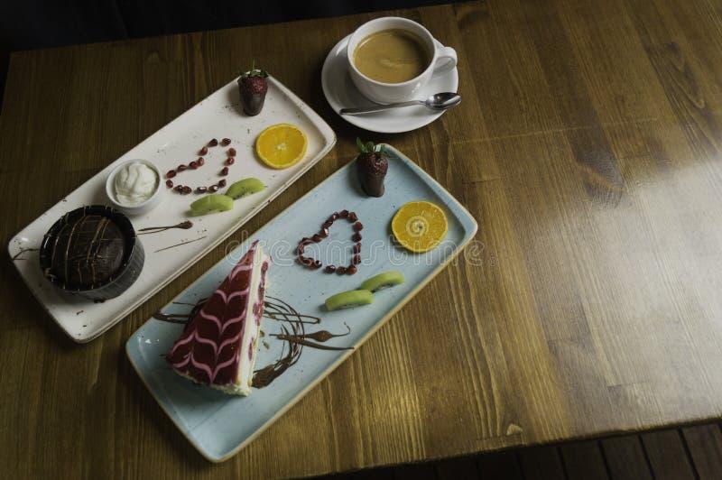 盘子在被切的巧克力蛋糕和饮料站立 免版税图库摄影