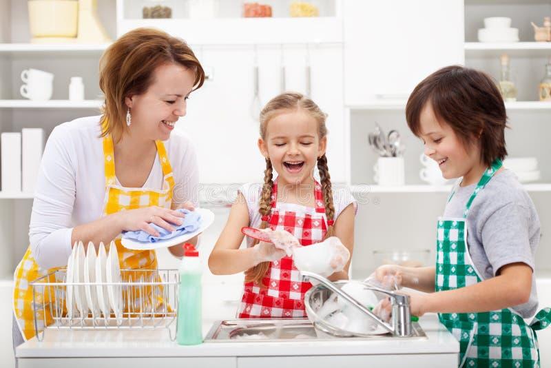 洗盘子的孩子和母亲 免版税库存图片