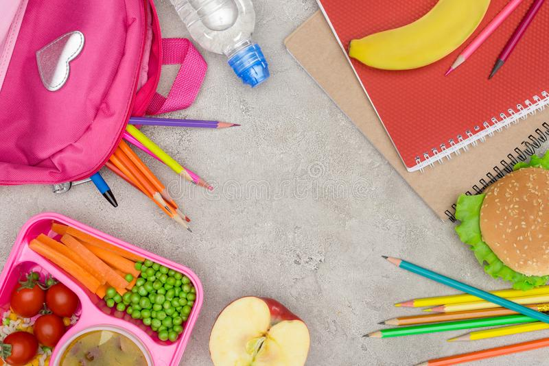 盘子顶视图有孩子的为学校、笔记本和铅笔吃午餐 免版税库存图片