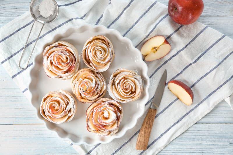盘用在桌上的鲜美玫瑰色形状的苹果酥皮点心 库存图片