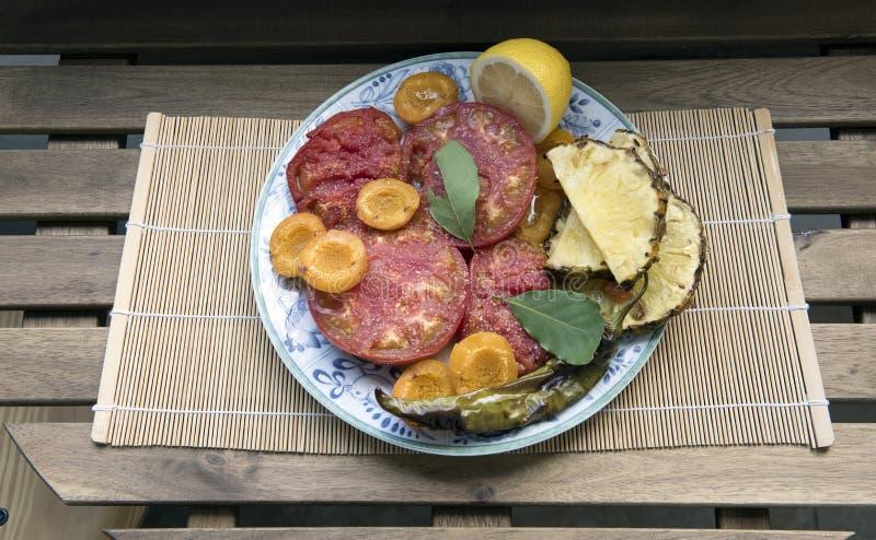 盘用煮熟的水果和蔬菜在桌上 免版税库存照片