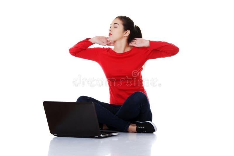 盘着腿坐与膝上型计算机的疲乏的妇女 免版税图库摄影