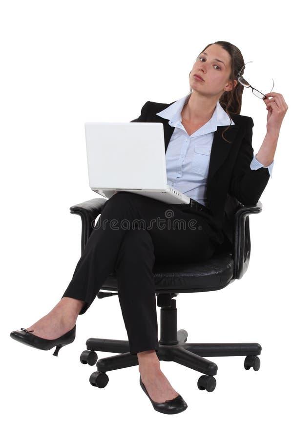 盘着腿坐确信的女实业家 库存图片