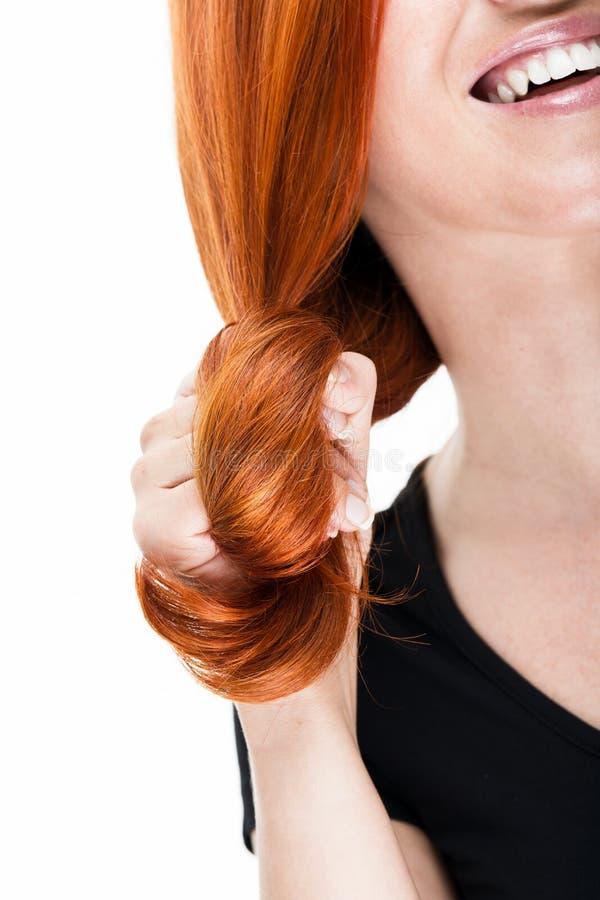 盘绕她的红色头发的笑的妇女 库存图片