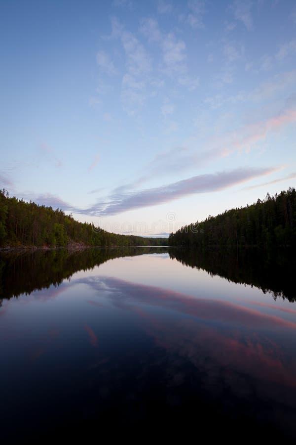 盛夏夜晚天空反射的镇静森林湖 库存照片