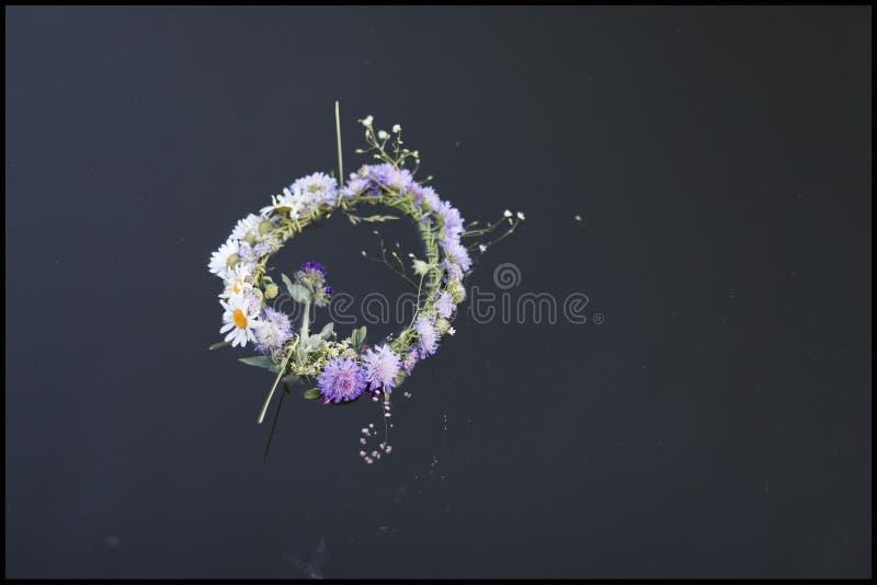 盛夏花花圈在黑暗的水中 免版税库存图片