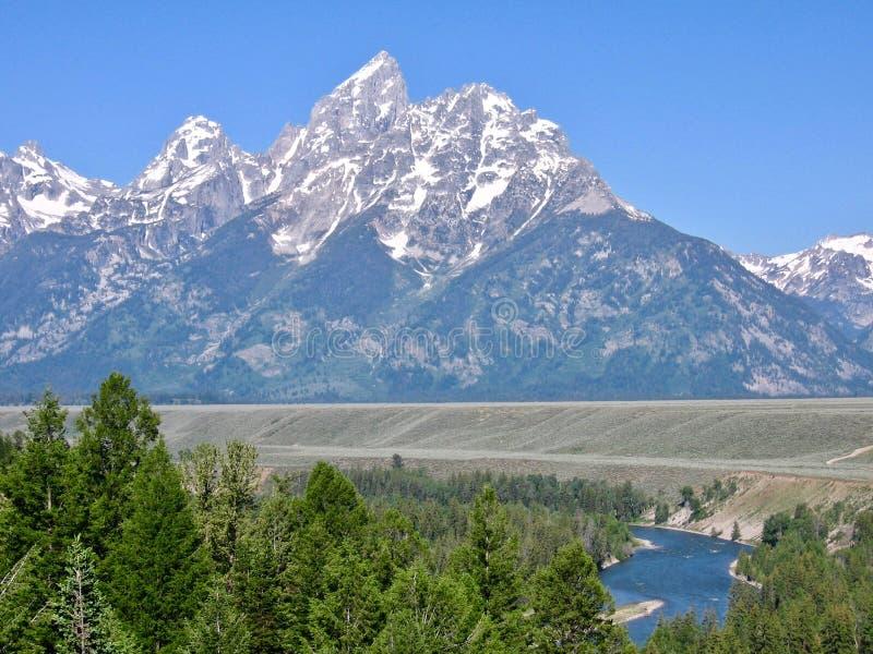 盛大Tetons国立公园在怀俄明,美国;与雪、太阳和河的印象深刻的山峰视图 库存照片