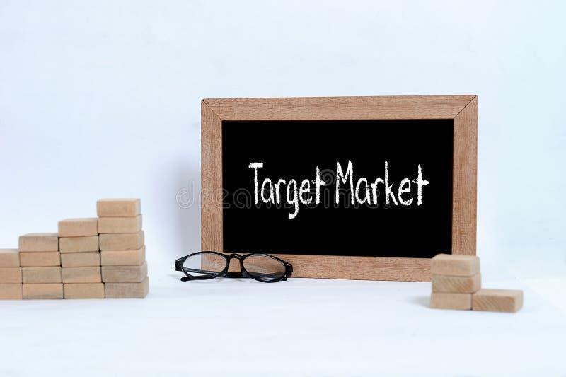 目标市场手写与在黑板的白色白垩 堆积作为步事务c的台阶标志的眼睛玻璃和木刻 免版税库存图片
