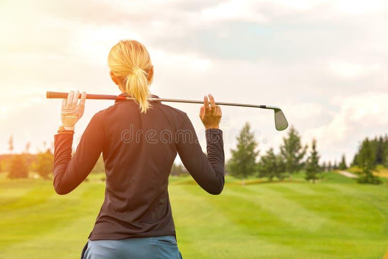 目标概念,拷贝空间 打高尔夫球时间的妇女拿着在绿色领域背景的高尔夫用品 对优秀的追求 库存图片