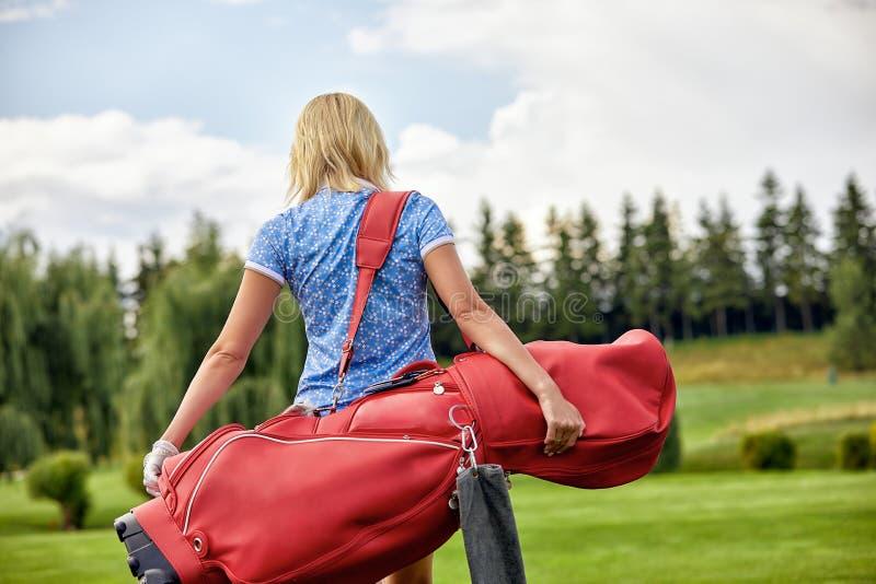 目标概念,拷贝空间 打高尔夫球时间的妇女拿着在绿色领域背景的高尔夫用品 对优秀的追求 免版税库存照片