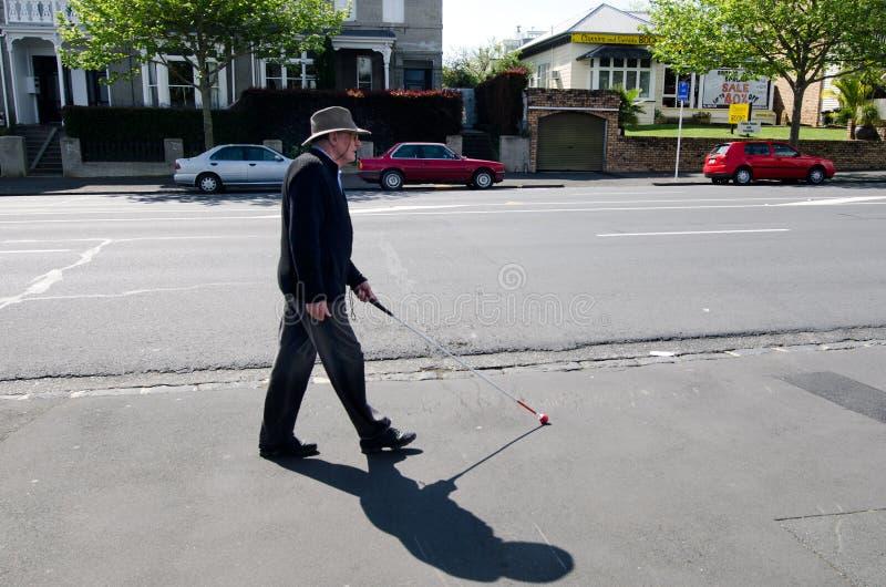 盲人走与在街道的藤茎 免版税图库摄影