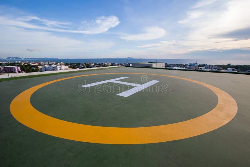 直升机停车处的标志在办公楼的屋顶 城市地平线空的方形的前面  免版税图库摄影