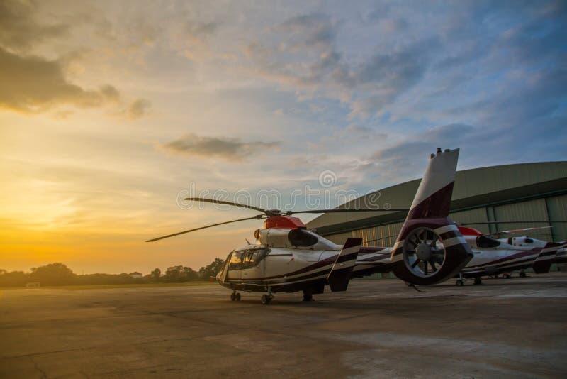 直升机或跑道剪影在停车场的有sunri的 免版税库存照片