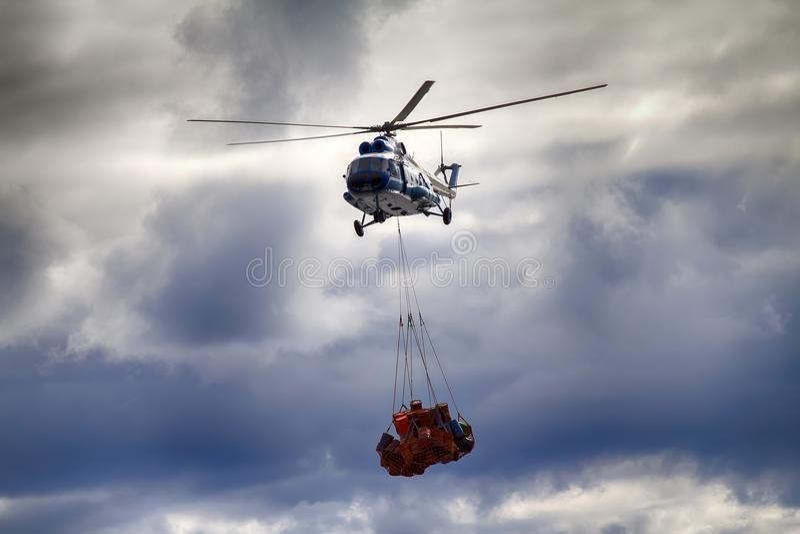 直升机运载吊索与空的金属桶的绳索滤网 库存图片