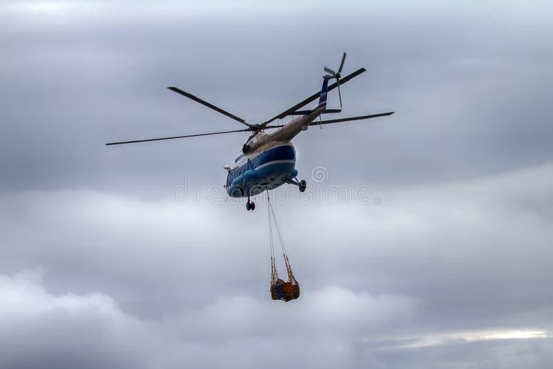 直升机运载吊索与空的金属桶的绳索滤网 免版税图库摄影
