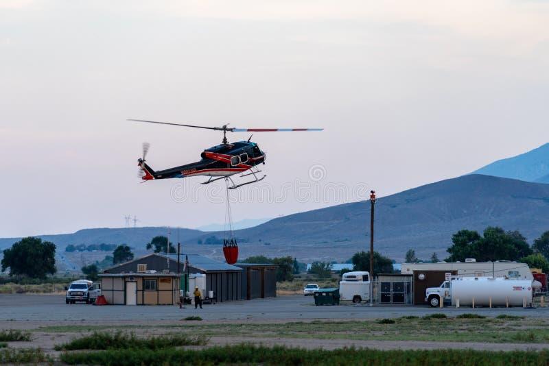 直升机飞行一个桶水到附近的加利福尼亚野火灭火 免版税库存照片