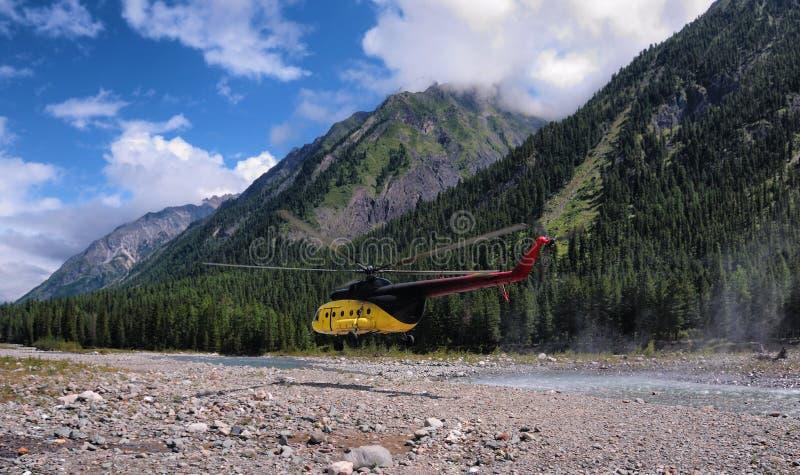 直升机飞行在山河 免版税库存照片