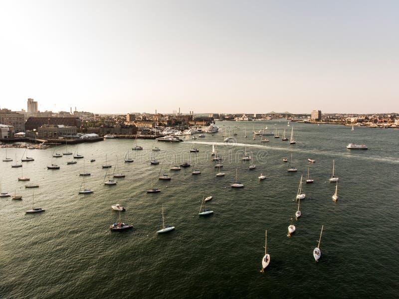 直升机飞行鸟瞰图图象波士顿麻省,在日落期间的美国怀有与小船在江边海湾附近 库存图片