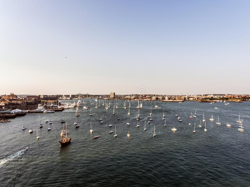 直升机飞行鸟瞰图图象波士顿麻省,在日落期间的美国怀有与小船在江边海湾附近 免版税图库摄影