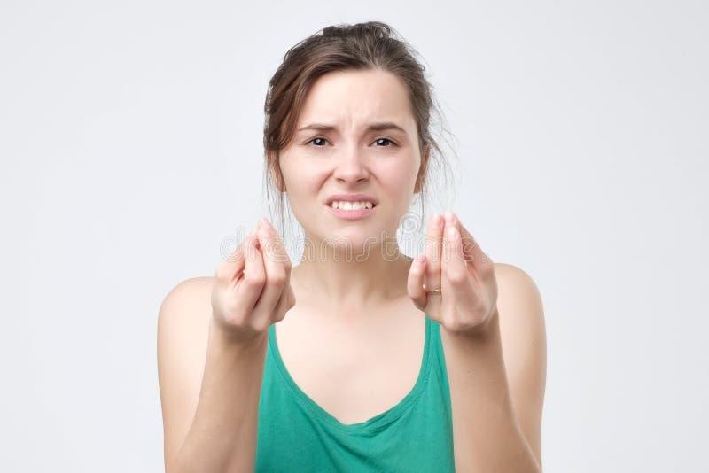 直向前看的妇女做一个典型的意大利姿态,皱眉的面孔和 免版税库存图片