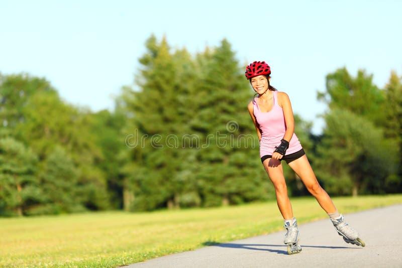 直排轮式溜冰鞋滑冰的妇女 免版税库存照片