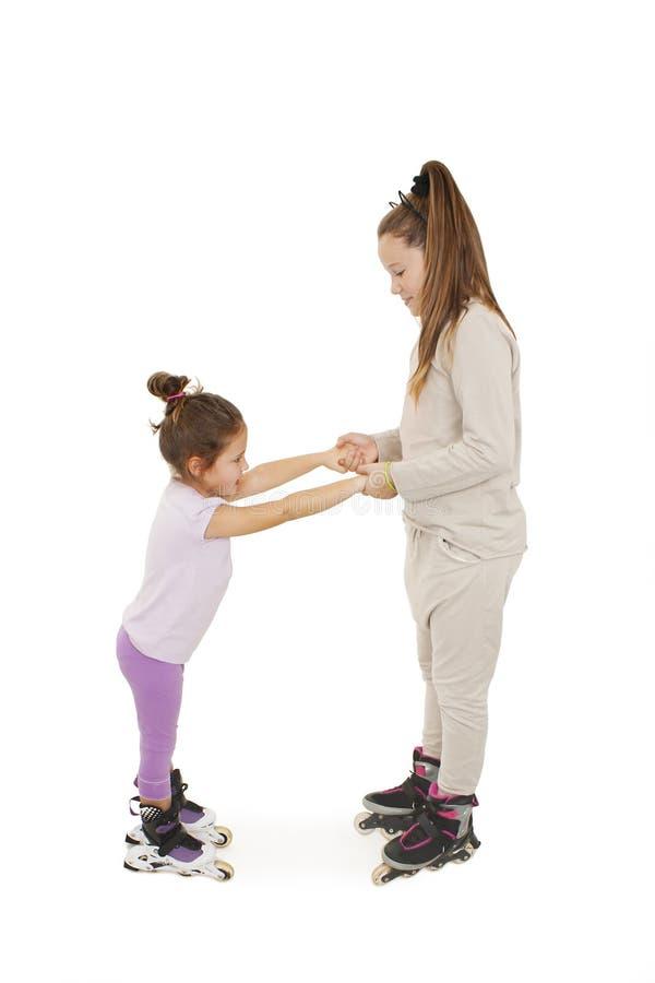 直排轮式溜冰鞋的一个微笑的学龄前儿童 她的姐妹握她的手,当设法鼓励她时 图库摄影