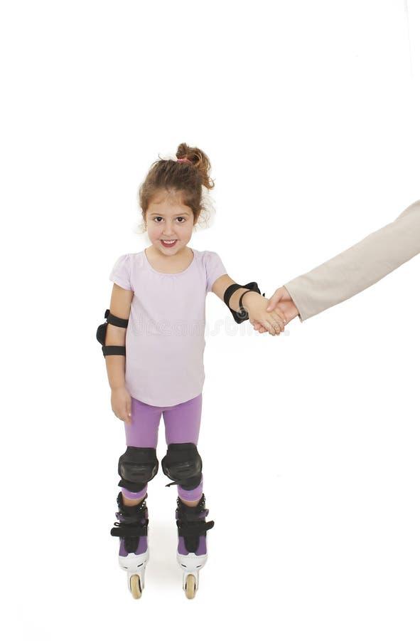 直排轮式溜冰鞋的一个微笑的学龄前儿童 她的姐妹握她的手,当设法鼓励她时 免版税库存图片